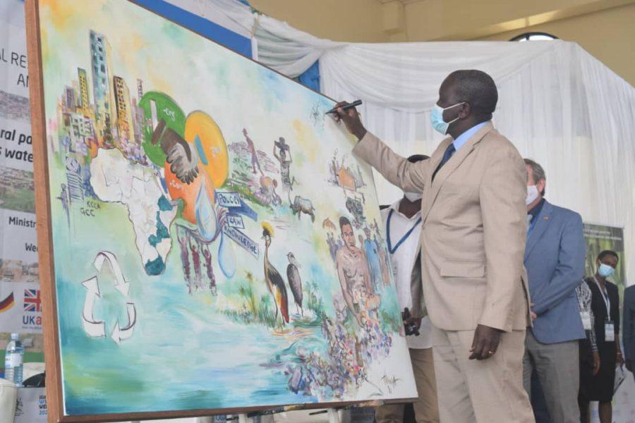Man signing an artwork piece on stewardship in Uganda